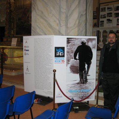 Luca in front of the panel of the exhibition.